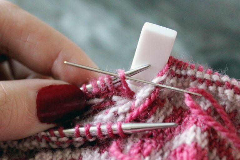 The tapestry needle has been inserted purlwise into the first stitch on the back needle