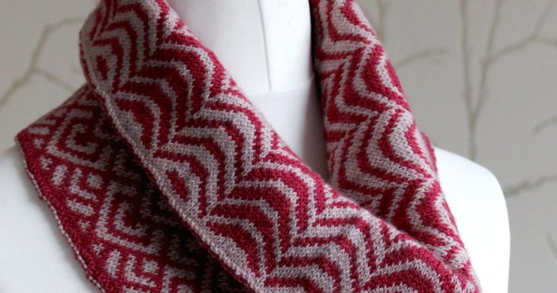 """A cowl with stranded knitting in red and pink yarn with a pattern made up of soft curves, folded over a pattern made up of interlocking """"V"""" shapes and scale shapes, modelled on a mannequin"""