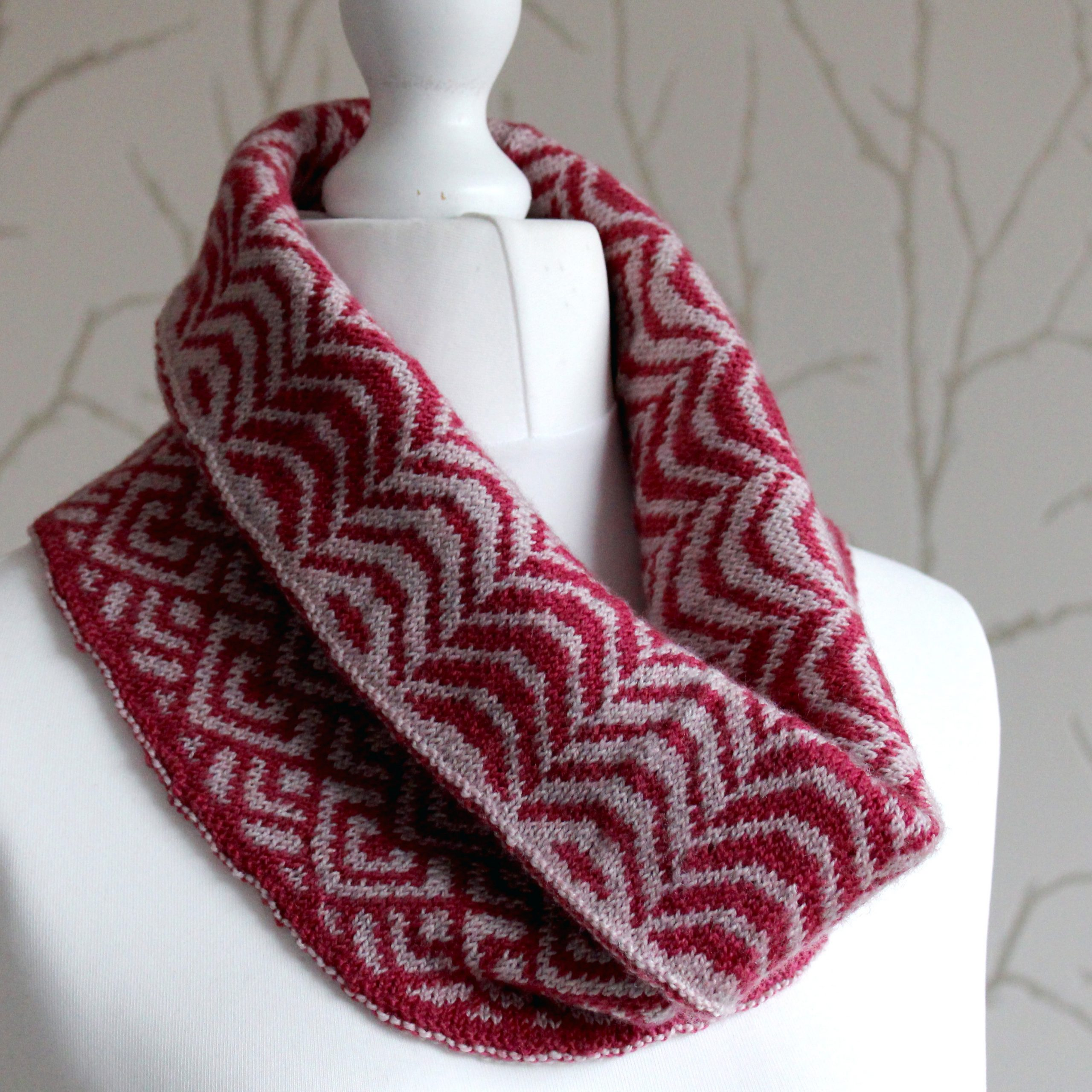 "A cowl with stranded knitting in red and pink yarn with a pattern made up of soft curves, folded over a pattern made up of interlocking ""V"" shapes and scale shapes, modelled on a mannequin"