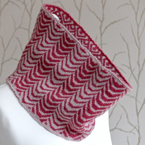 A cowl with stranded knitting in red and pink yarn with a pattern made up of soft curves, modelled on a mannequin