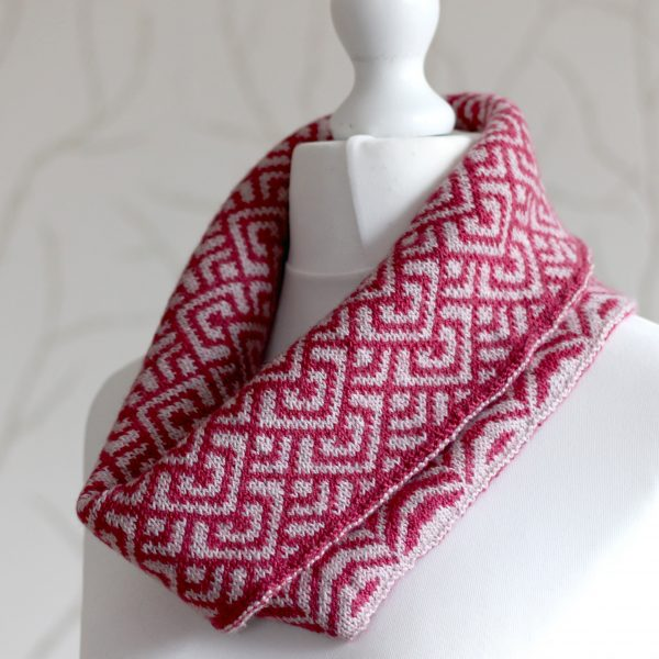 "A cowl with stranded knitting in red and pink yarn with a pattern made up of interlocking ""V"" shapes and scale shapes, folded over a pattern made up of soft curves, modelled on a mannequin"