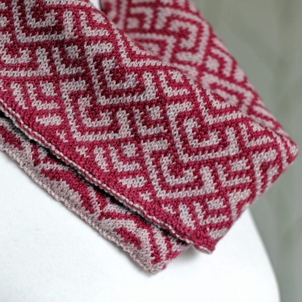 "A close up of a cowl with stranded knitting in red and pink yarn with a pattern made up of interlocking ""V"" shapes and scale shapes, folded over a pattern made up of soft curves, modelled on a mannequin"