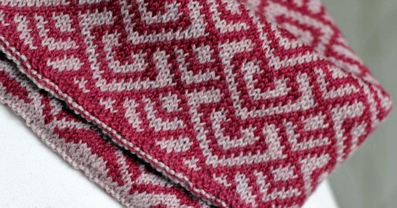 """A close up of a cowl with stranded knitting in red and pink yarn with a pattern made up of interlocking """"V"""" shapes and scale shapes, folded over a pattern made up of soft curves, modelled on a mannequin"""
