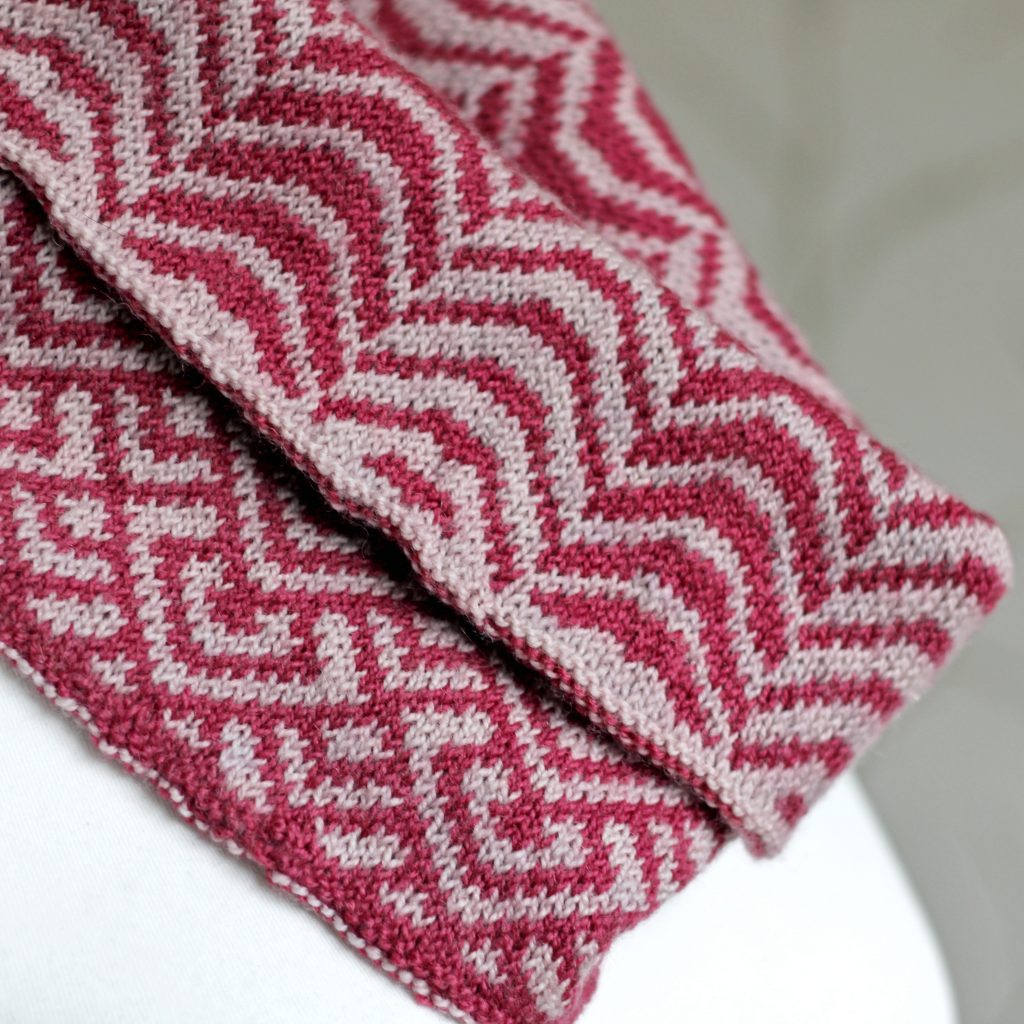 """A close up of a cowl with stranded knitting in red and pink yarn with a pattern made up of soft curves, folded over a pattern made up of interlocking """"V"""" shapes and scale shapes, modelled on a mannequin"""