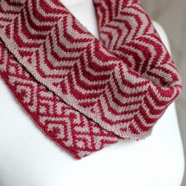 "A close up of a cowl with stranded knitting in red and pink yarn with a pattern made up of soft curves, folded over a pattern made up of interlocking ""V"" shapes and scale shapes, modelled on a mannequin"