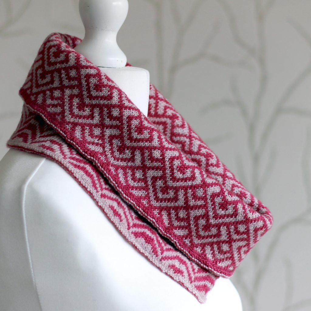 """A cowl with stranded knitting in red and pink yarn with a pattern made up of interlocking """"V"""" shapes and scale shapes, folded over a pattern made up of soft curves, modelled on a mannequin"""