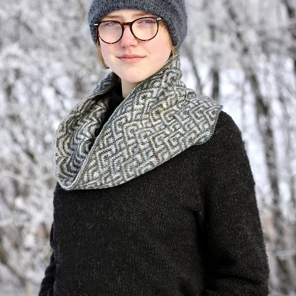"""A cowl with stranded knitting in grey and white speckled yarn with a pattern made up of interlocking """"V"""" shapes and scale shapes, modelled by a girl wearing glasses"""