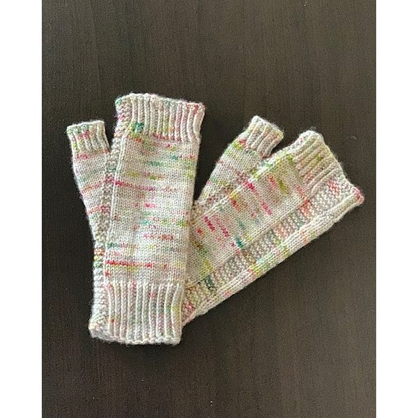 A pair of fingerless mitts knit in white speckled yarn showing the garter stitch columns around the thumb gusset and the outside of the hand