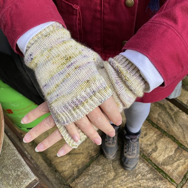 Two hands wearing a pair fingerless mitts knit in yellow and grey yarn with colourful strips showing the garter stitch columns around the thumb gusset and the outside of the hand