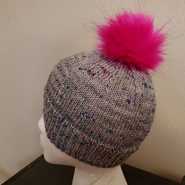 A grey hat with colourful speckles and a pink faux fur pompom on a foam head