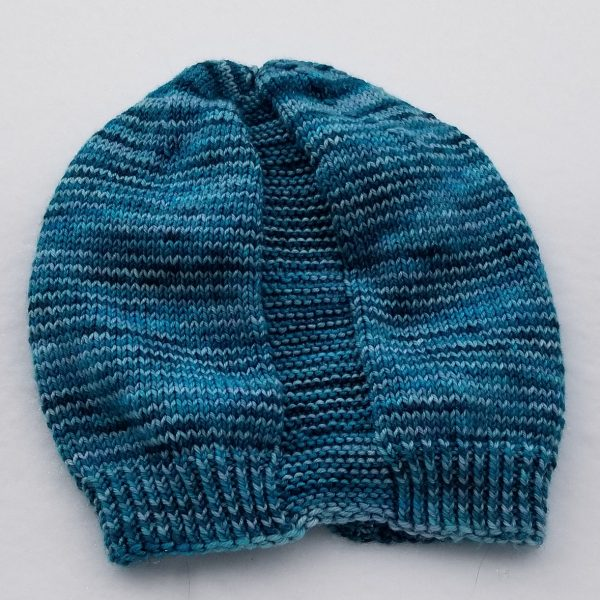 A hat knit in shades of blue with two garter stitch columns laid flat
