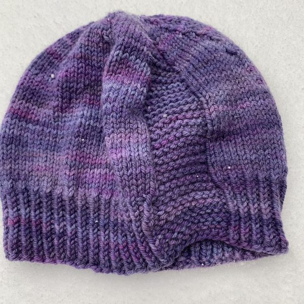 A hat knit in shades of purple with two garter stitch columns laid flat
