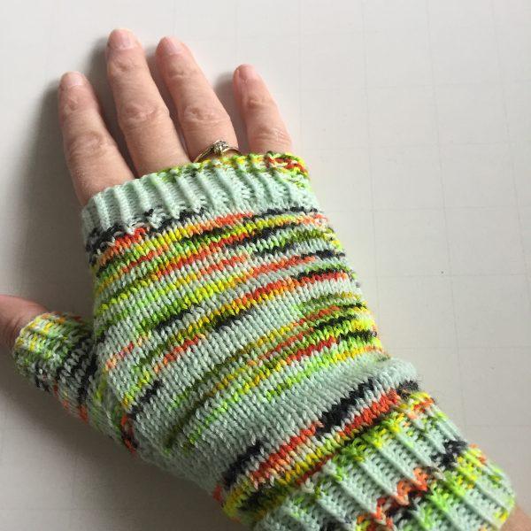 A hand wearing a fingerless mitt knit in variegated yarn