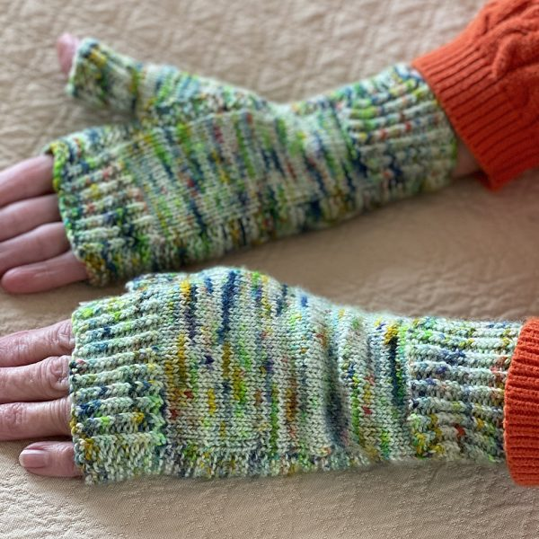 Two hands wearing a pair fingerless mitts knit in variegated yarn with colourful strips showing the garter stitch columns around the thumb gusset and the outside of the hand