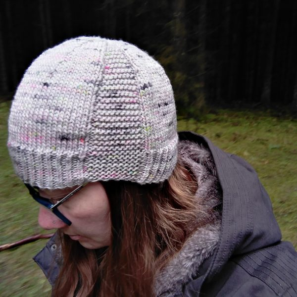 A woman wearing a beanie hat knit in grey yarn with colourful speckles and garter stitch columns up each side
