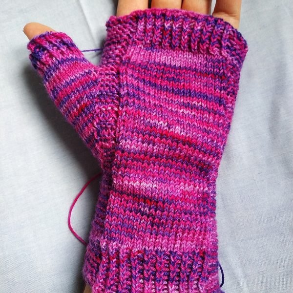 A hand wearing a fingerless mitt knit in variegated yarn showing the garter stitch columns around the thumb gusset and the outside of the hand