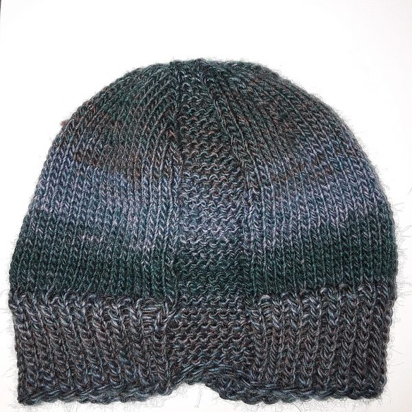A hat knit with stripes in shades of brown and green and two garter stitch columns laid flat