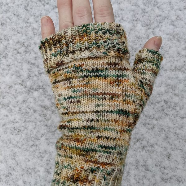 A hand wearing a fingerless mitt knit in variegated yarn showing the garter stitch columns around the thumb gusset and the outside of the hand and a folded down cuff