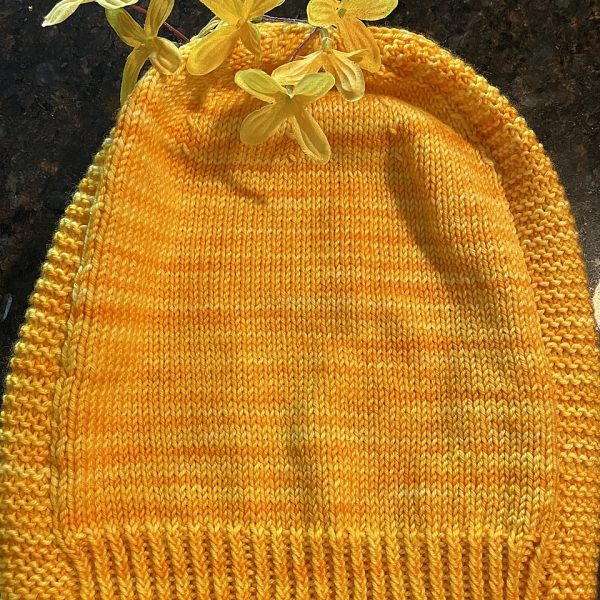 A hat knit in shades of yellow with two garter stitch columns laid flat