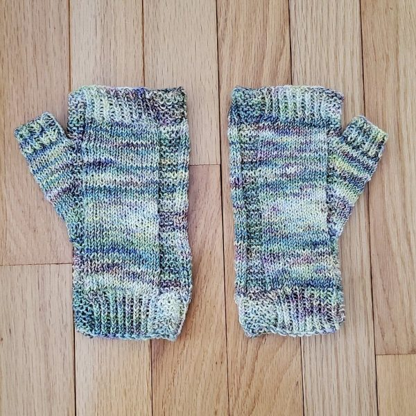 A pair of fingerless mitts knit in pastel yarn showing the garter stitch columns around the thumb gusset and the outside of the hand
