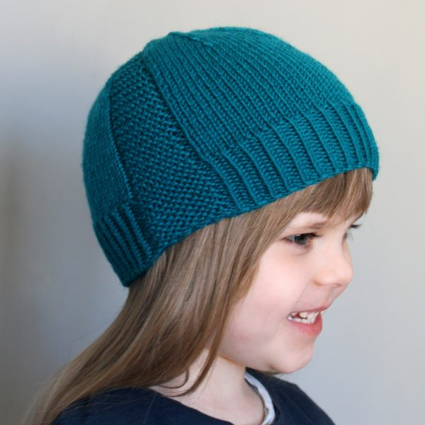 A young girl wearing a beanie hat knit in teal yarn with garter stitch columns up each side