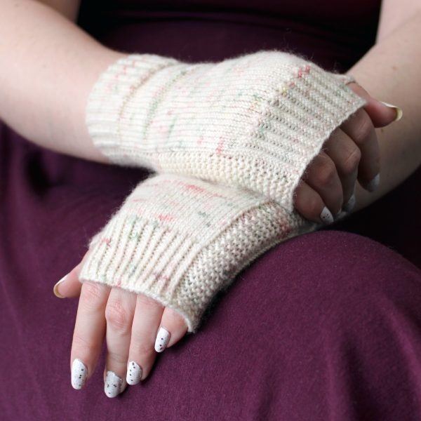 Two hands clasped showing the garter stitch columns around the outside of the hand of a pair of fingerless mitts knit in cream yarn with pink and green speckles