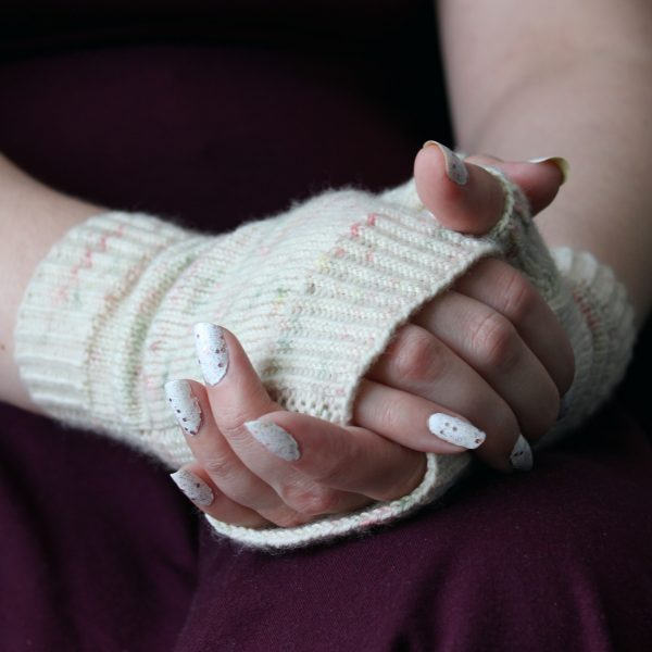 Two hands clasped showing the garter stitch column around the outside of one hand and the twisted rib cuff of a pair of fingerless mitts knit in cream yarn with pink and green speckles