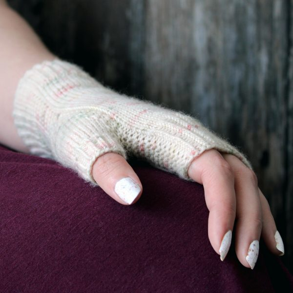 A hand showing the garter stitch column wrapping around the thumb gusset of a fingerless mitt knit in cream yarn with pink and green speckles