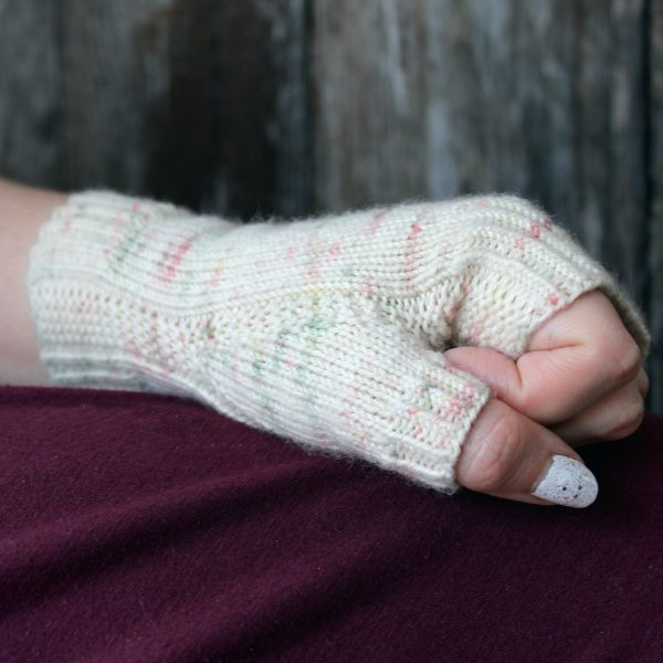A hand making a fist showing the garter stitch column wrapping around the thumb gusset of a fingerless mitt knit in cream yarn with pink and green speckles