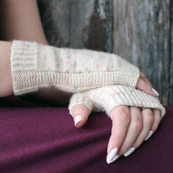 Two hands clasped showing the garter stitch column around the outside of one hand and the column wrapping around the thumb gusset of the other hand of a pair of fingerless mitts knit in cream yarn with pink and green speckles