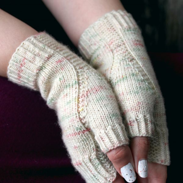 Two hands pressed together showing the garter stitch columns wrapping around the thumb gussets of a pair of fingerless mitts knit in cream yarn with pink and green speckles