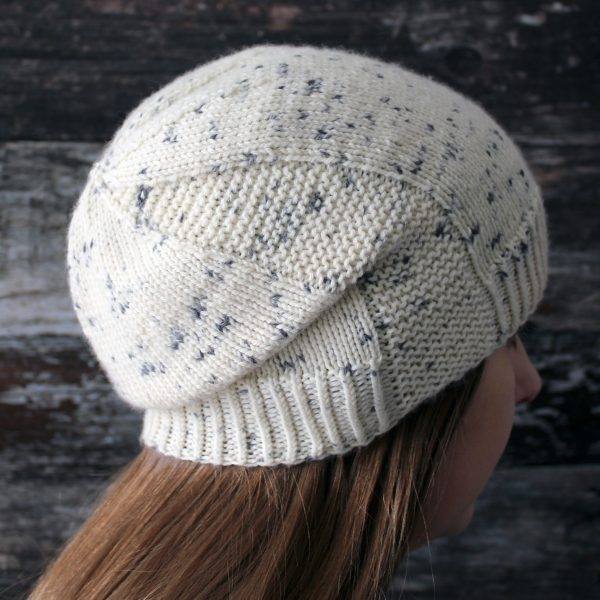 A woman wearing a slouchy hat knit in white yarn with black speckles and garter stitch columns up each side