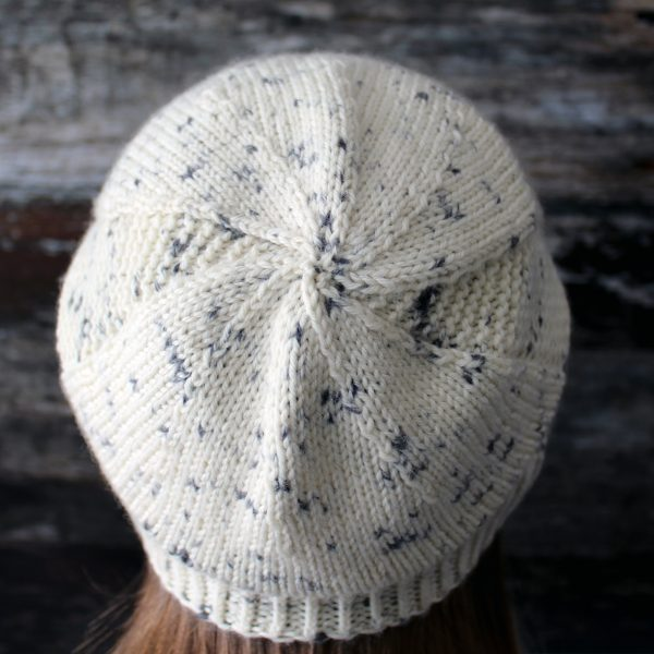 The crown of a slouchy hat knit in white yarn with black speckles and garter stitch columns up each side