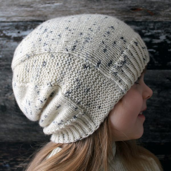 A young girl wearing a slouchy hat knit in white yarn with black speckles and garter stitch columns up each side
