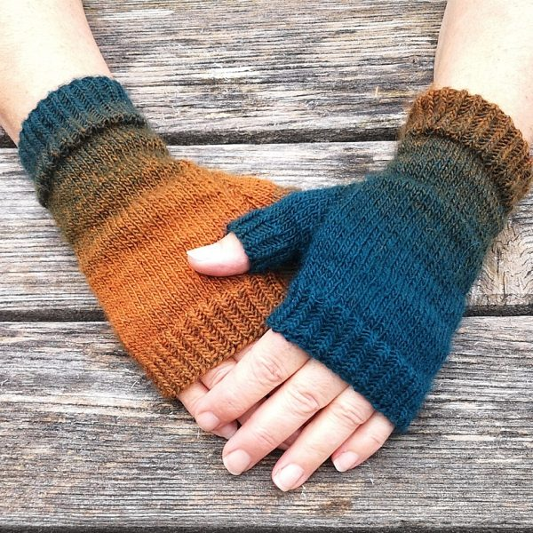 Two hands wearing a pair fingerless mitts knit in gradiented yarn with colourful strips showing the garter stitch columns around the thumb gusset and the outside of the hand