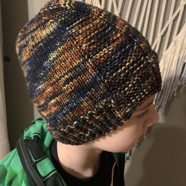 A boy wearing a beanie hat knit in variegated yarn with garter stitch columns up each side