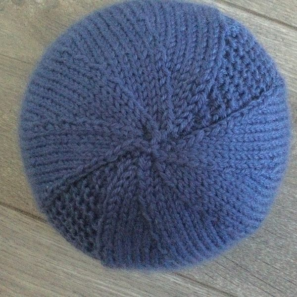 The crown of a beanie hat knit in blue yarn with garter stitch columns up each side