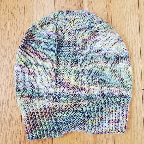 A hat knit with pastel colours and two garter stitch columns laid flat