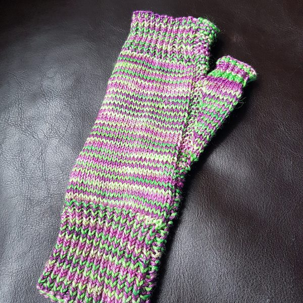 A fingerless mitt knit in purple and green yarn showing the garter stitch columns around the thumb gusset and the outside of the hand