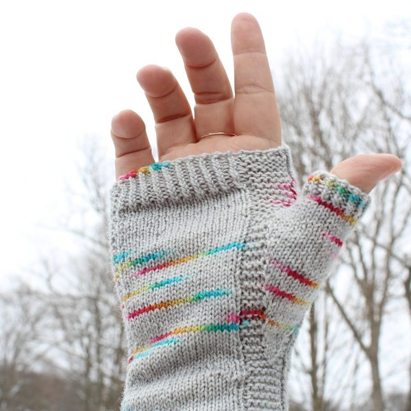 A hand wearing a fingerless mitt knit in grey yarn with colourful strips showing the garter stitch columns around the thumb gusset and the outside of the hand