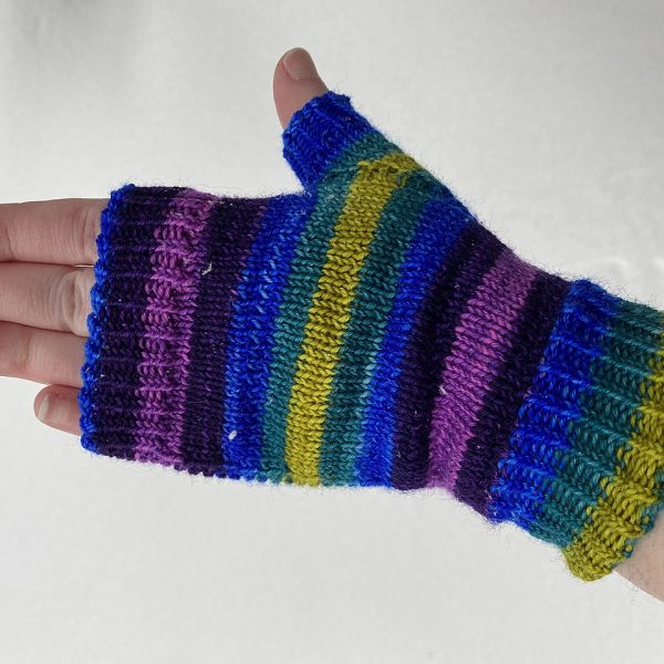 A hand wearing a fingerless mitt knit in striped yarn with colourful strips showing the garter stitch columns around the thumb gusset and the outside of the hand