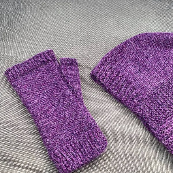 A fingerless mitt knit in purple yarn showing the garter stitch columns around the thumb gusset and the outside of the hand