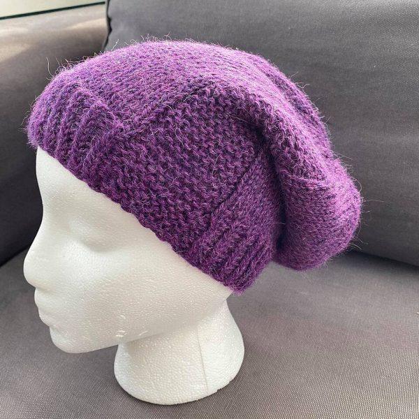 a slouchy hat knit in purple yarn with garter stitch columns up each side on a foam head
