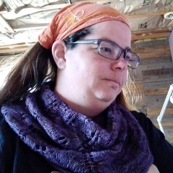 A model wearing a cowl in purple yarn with diamond shaped lace leaves and a wide garter stitch border