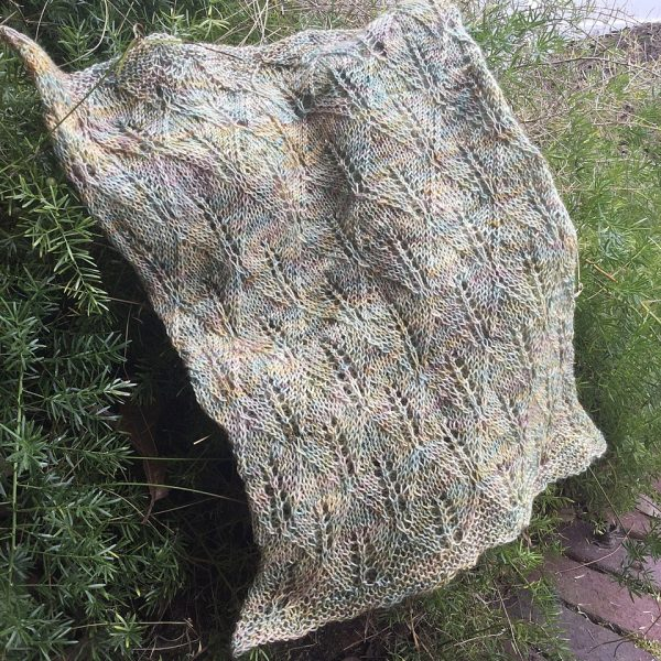 A pale variegated coloured cowl with diamond shaped lace leaves and wide garter stitch borders draped over a bush