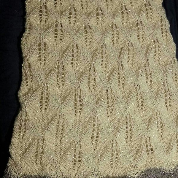 A pale yellow coloured cowl with sparkling yarn, with diamond shaped lace leaves and wide garter stitch borders laid flat