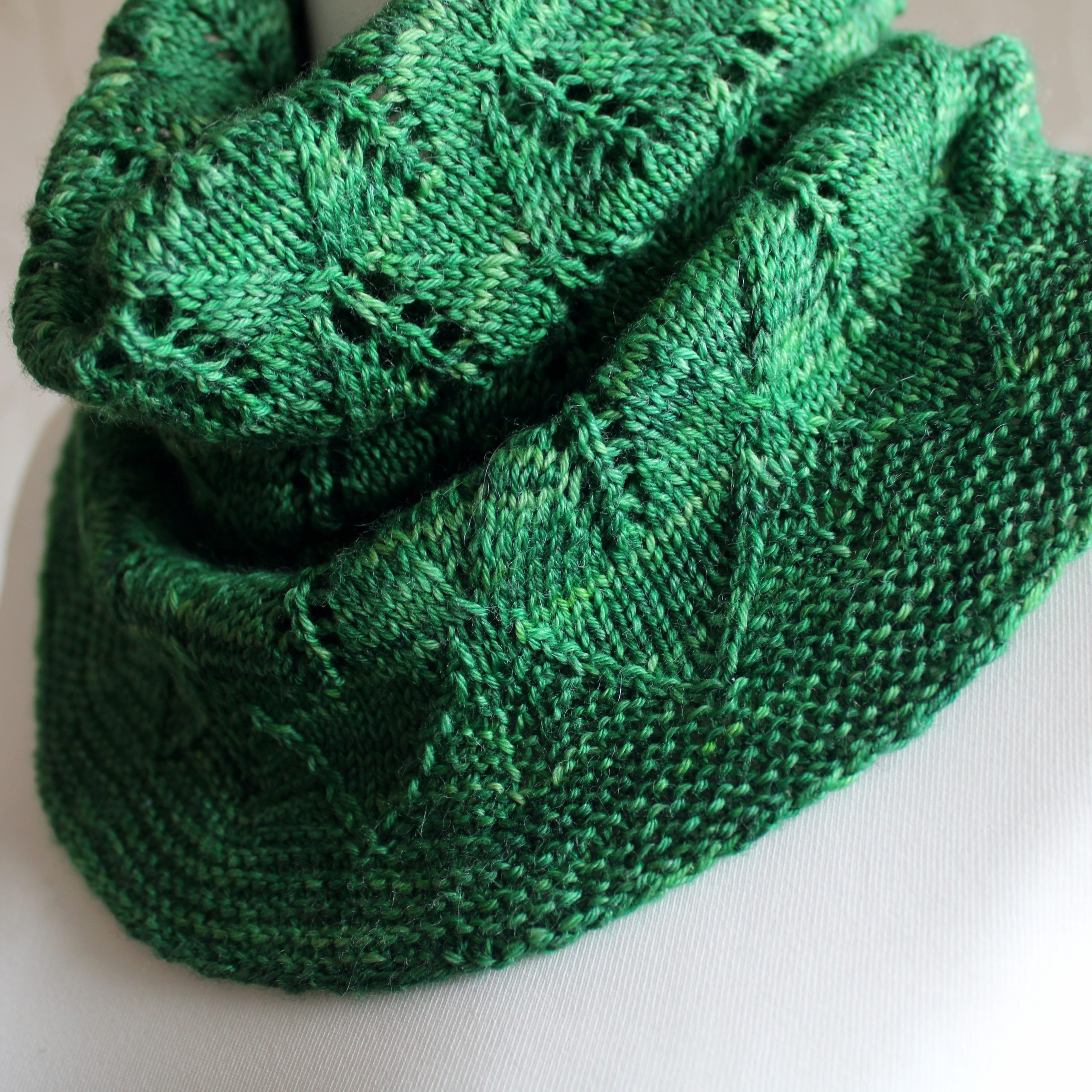 A close up on a green cowl with diamond shaped leaves and a wide lace border modelled on a mannequin