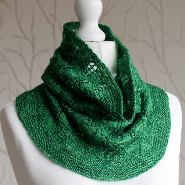 A green cowl with diamond shaped leaves and a wide lace border modelled on a mannequin