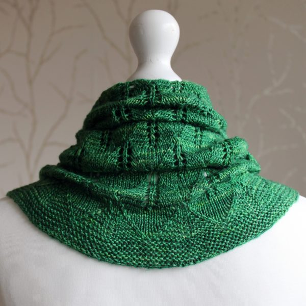 The back of a green cowl with diamond shaped leaves and a wide lace border modelled on a mannequin