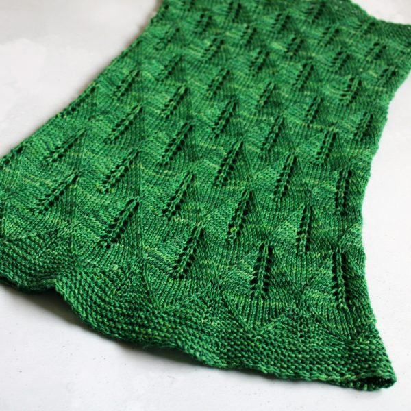 A green cowl with diamond shaped lace leaves and wide garter stitch borders laid flat to show the tapered shape and the increasing leaf size from top to bottom
